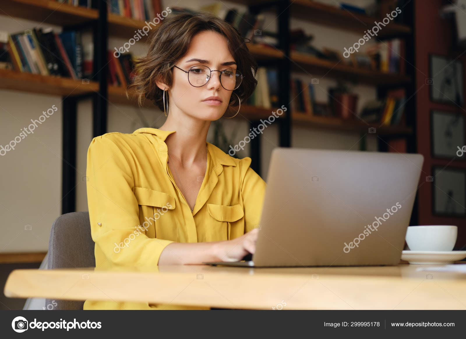 Stock photo young serious businesswoman in eyeglasses.