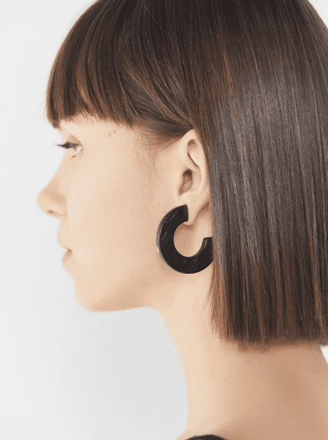 The girl with a blunt bob with massive marble earrings in deep dark color.