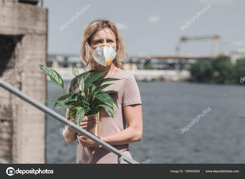 Woman in protective mask holding potted plant on bridge, air pollution concept – stock image