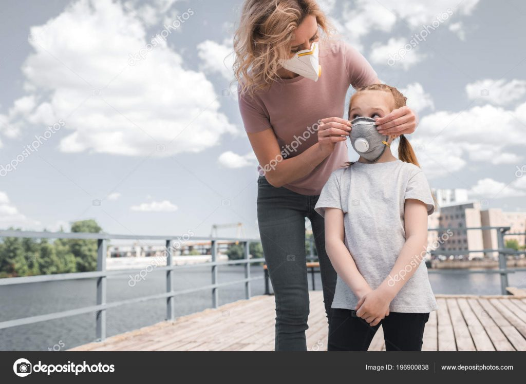 Mother and daughter in protective masks on bridge, air pollution concept – stock image