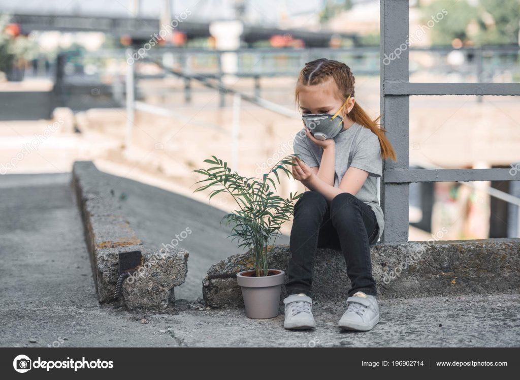 Child in protective mask looking at green potted plant, air pollution concept – stock image