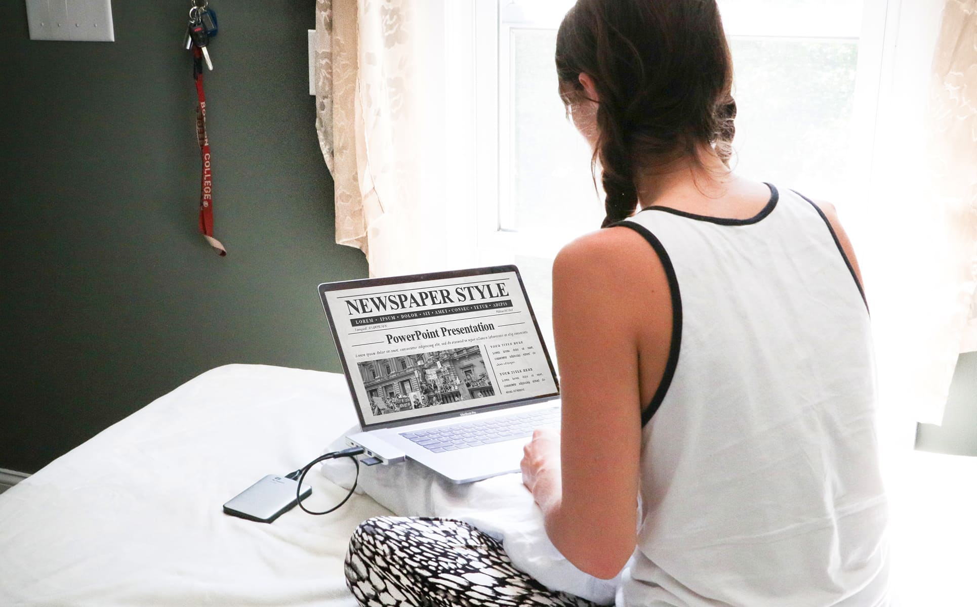 The girl sits at the computer and works on the presentation with the newspaper PowerPoint template.
