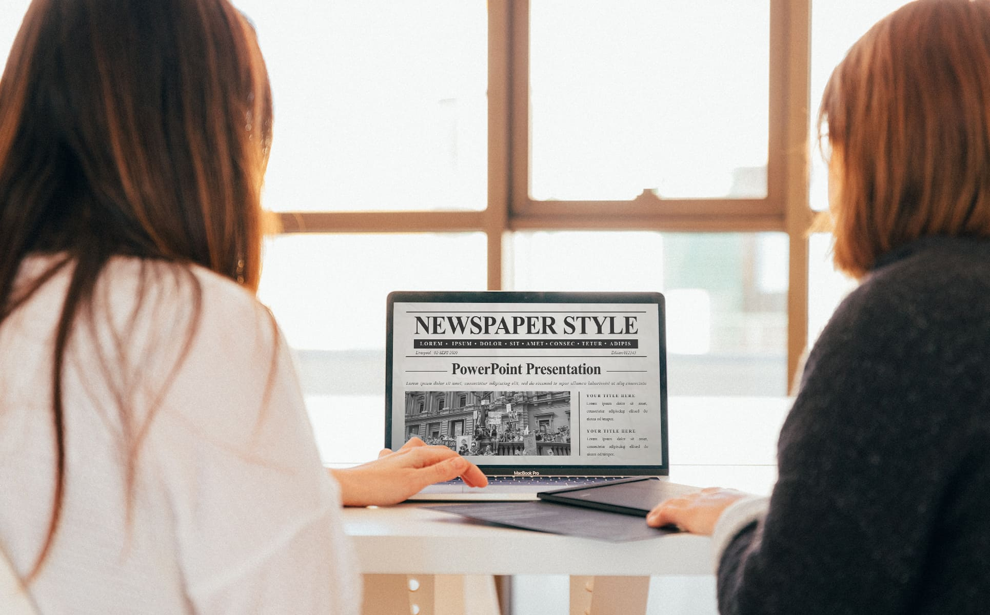 Two women are watching the Newspaper PowerPoint presentation.