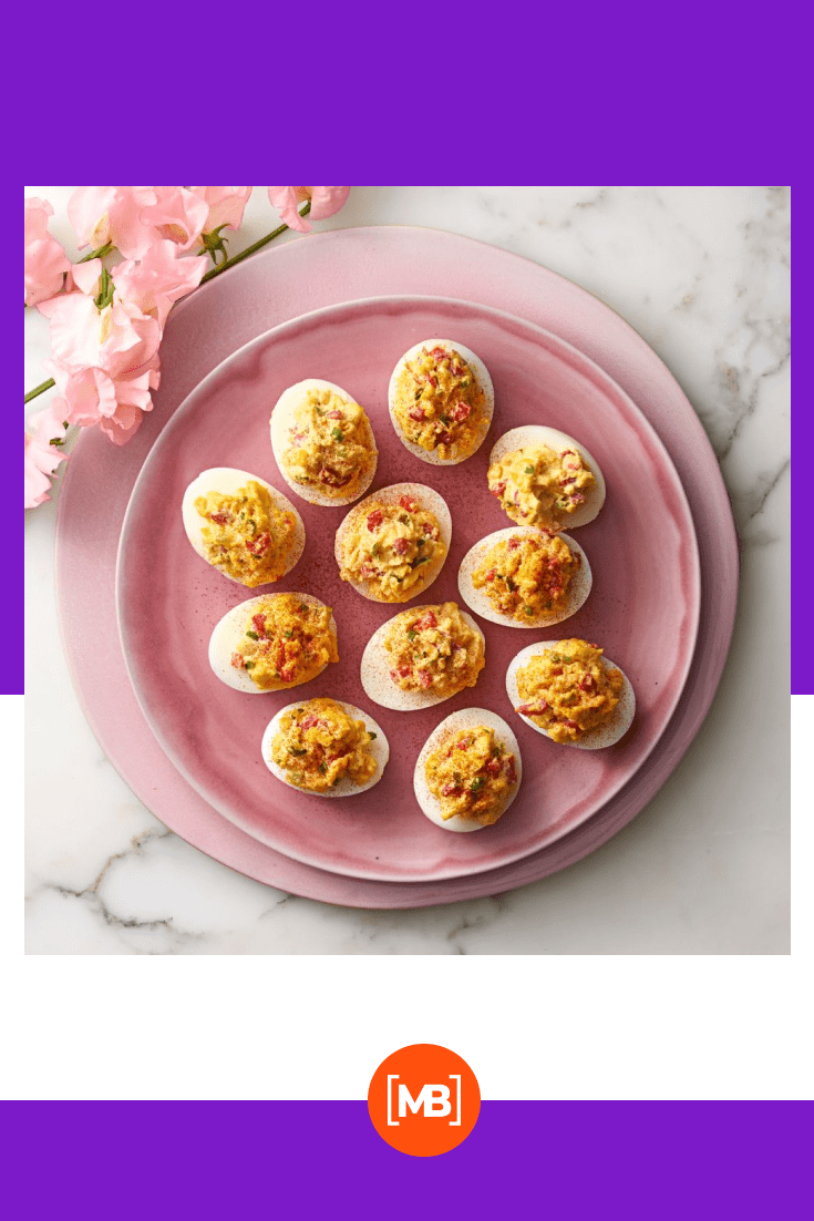 Pimiento-Cheese Deviled Eggs. Such delicious stuffed eggs on a pink plate.