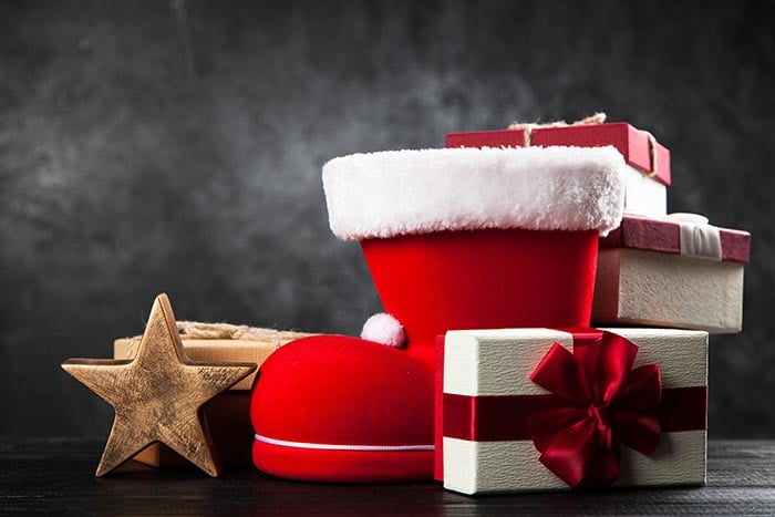 Santa's shoe with gifts boxes on dark background