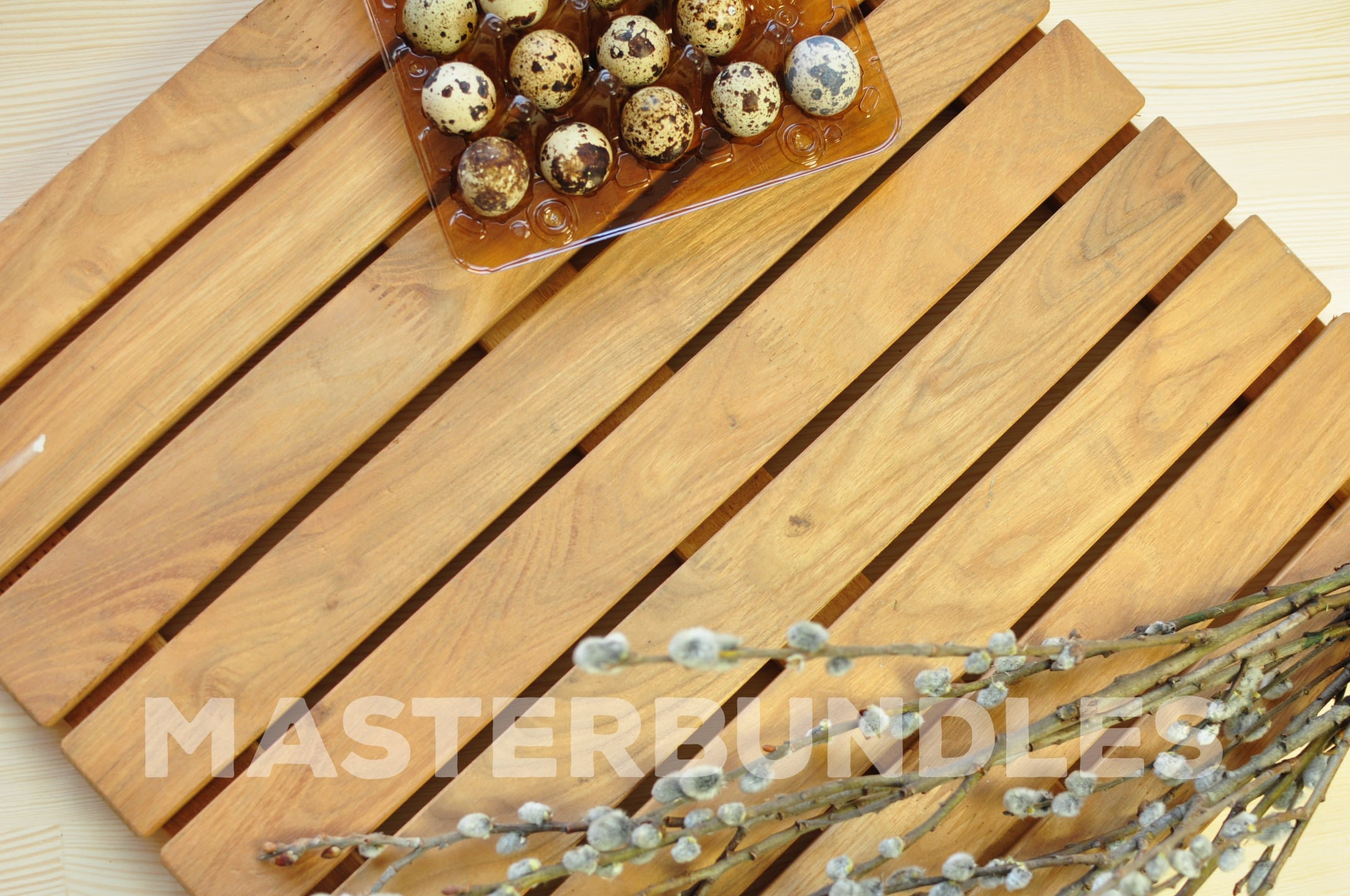 Quail eggs and pussy willow on a wooden surface.