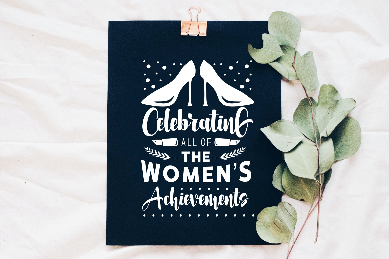 Black plaque with a gold holder and a white inscription about the celebration of women's day. Women's Day Quotes.
