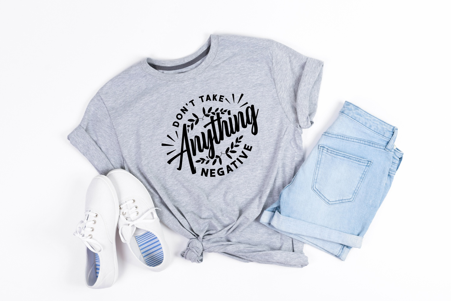A casual set for walking: a gray T-shirt with a lettering, white sneakers and denim shorts.