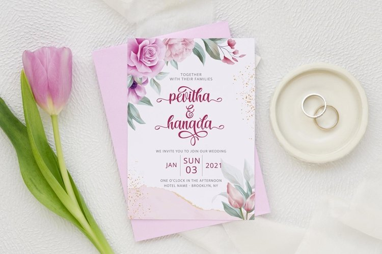 Gentle wedding invitation and wedding rings next to it.