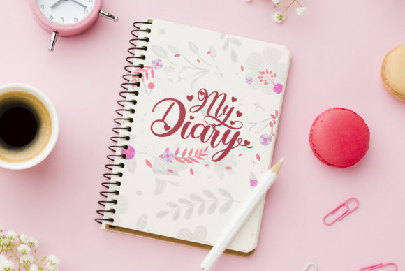 Pink background, pink alarm clock and pink diary. Purely girly mood.