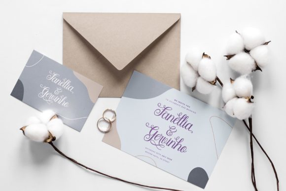 Wedding invitations and next to wedding rings.