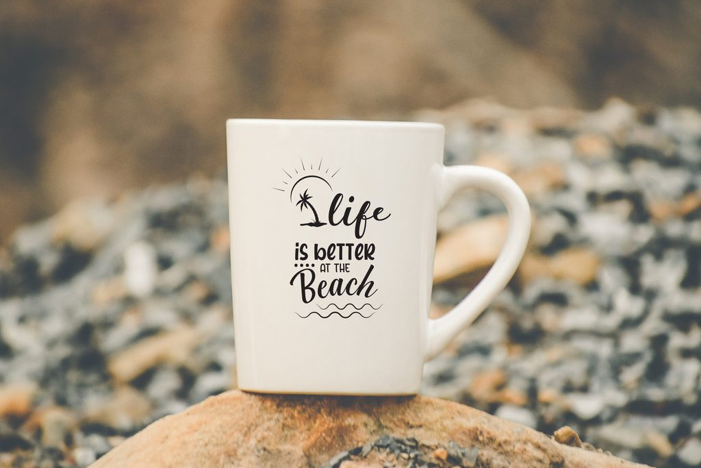 A white cup stands on a stone and has an inscription about the beach on it. width=
