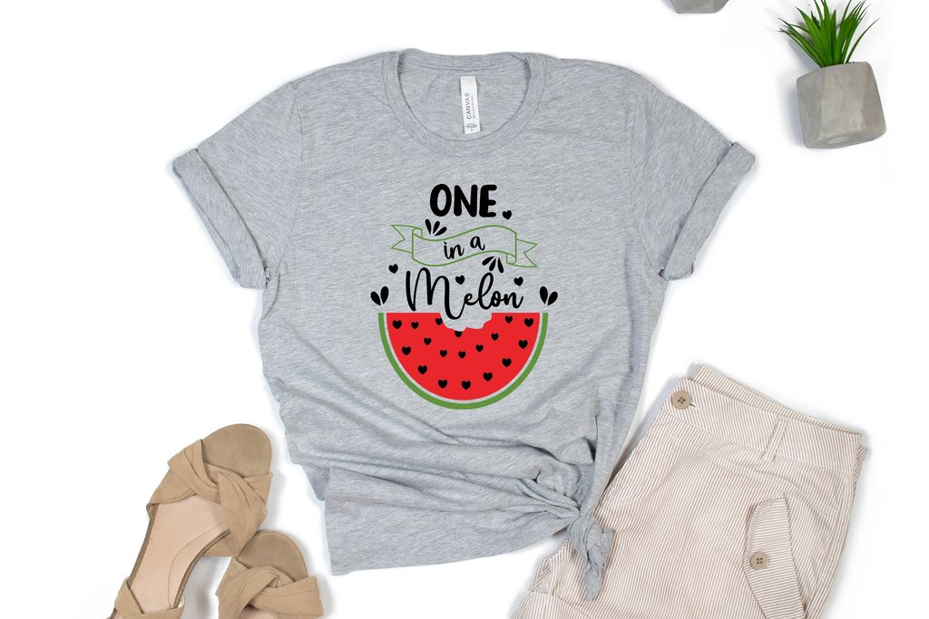 A gray T-shirt with a picture of a watermelon and light-colored trousers.