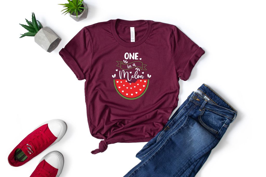 Dark jeans and a burgundy T-shirt with a picture of a watermelon.