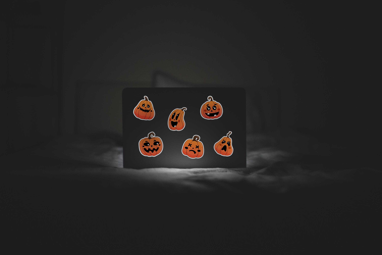 Halloween pumpkin stickers on dark background.